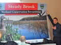 NL-EHJV Program Manager, Jonathan Sharpe presenting a road sign to Town of Steady Brook during municipal stewardship agreement signing ceremony in 2011/Tyler Dyke